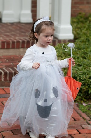 Little girl in witch costume having fun at Halloween trick or treat