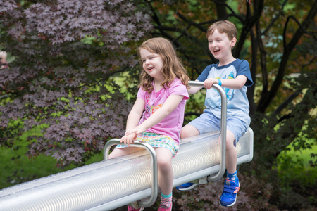 cute guy: Two cute pre-school children sitting on a seesaw