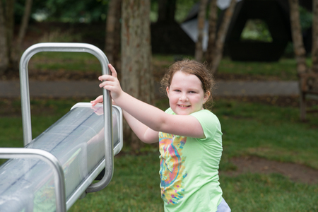Smiling attractive young girl holding a see-saw Stock Photo