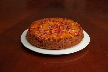 Cake with nectarines on white plate on top of dining table