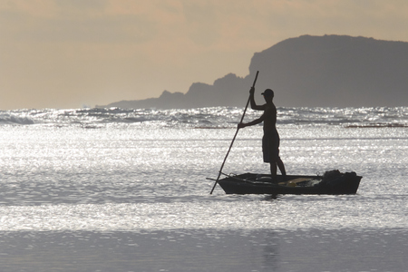poling: Silhouette of Fisherman Poling at Sunrise