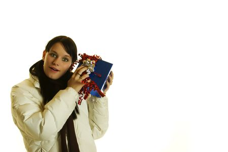 feliz: Attractive girl wearing winter coatand scarf shaking a christmas gift on white background