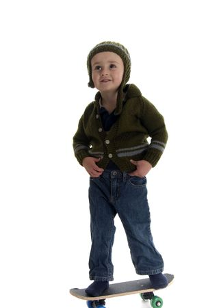 2 year old with sweater and hat stands on skateboard Imagens