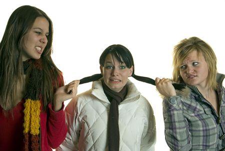 Two catty girls pull hair and bully third girl  Zdjęcie Seryjne