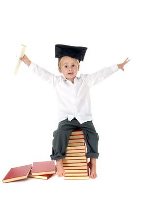 Happy & Cute toddler sits on stack of books wearing graduation cap holding diploma with hands in air