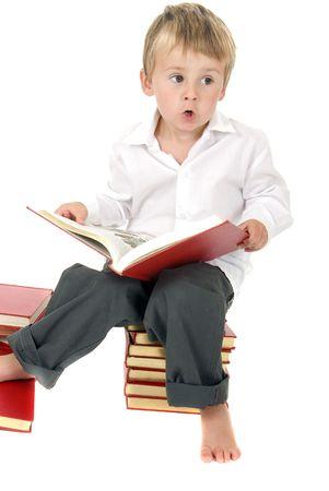 かわいいと勤勉の幼児は書籍のスタック上に座っている間 outloud を読み取ります。 幼児教育のテーマ 写真素材