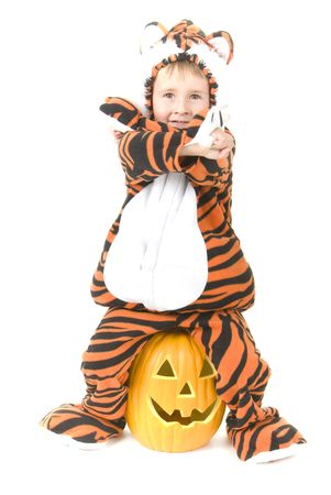 Toddler in Tiger costume sits on pumpkin.  Halloween theme