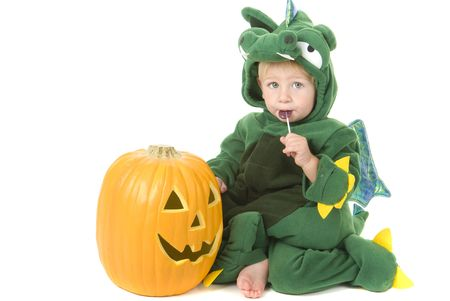 Halloween theme toddler eats candy beside pumpkin wearing dragon costume