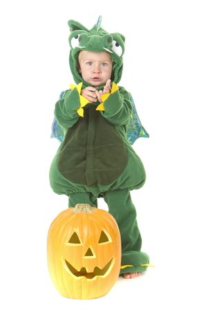 lolli: Halloween theme toddler holds hand out for candy beside pumpkin wearing dragon costume Stock Photo