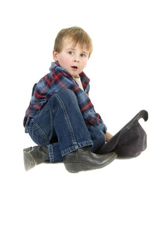 preschooler cowboy sits on floor with leather boots and black cowboy hat