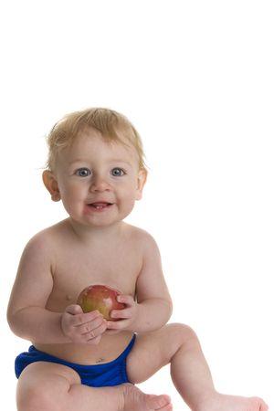 Happy baby holds and eats apple Zdjęcie Seryjne