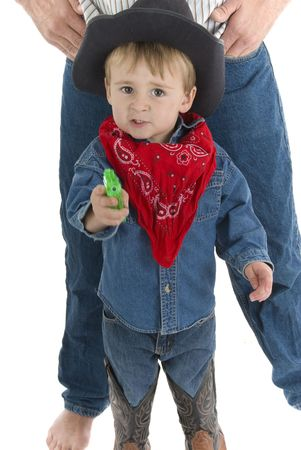 hankerchief: Little cowboy points squirt gun towards camera while protecting his dad Stock Photo