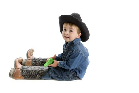 Toddler cowboy sits on floor with squirt gun and too big dads boots photo