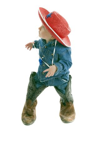 Adorable toddler cowboy wears too big leather boots looks toward left