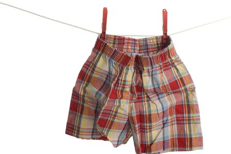 Red pair of boxer shorts hang on laundry line