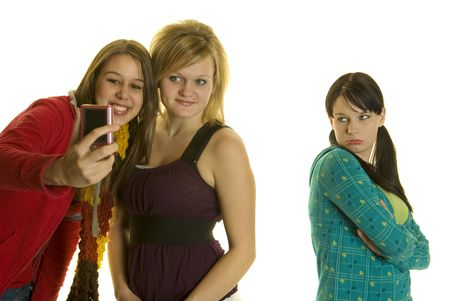 Two girls take photos with cell phone while leaving out a third girl