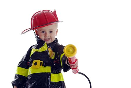 to believe: Little boy fire fighter points water sprayer at camera