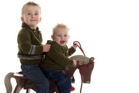 Adorable brothers share riding on rocking horse Stock Photo - 6311976