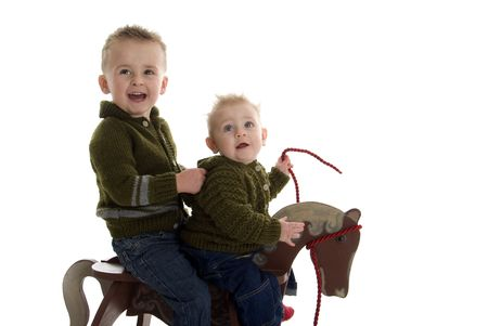 Adorable brothers share riding on rocking horse Zdjęcie Seryjne