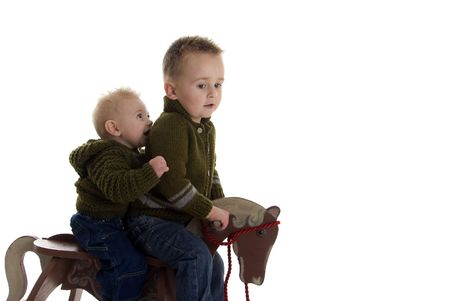 Adorable brothers share riding on rocking horse photo