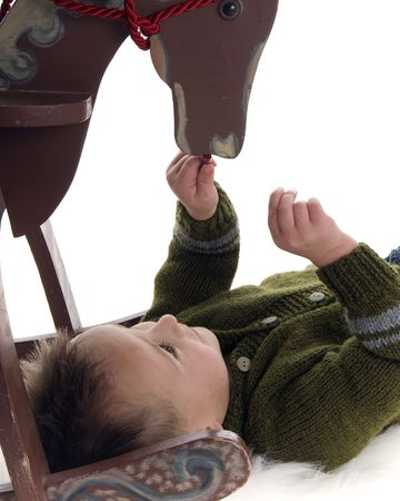 Cute little boy plays with rocking horse photo
