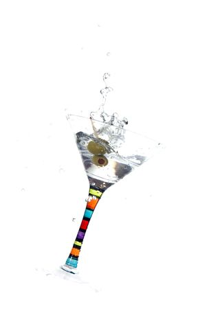 olive falls into martini glass creating a splash and glass to tip