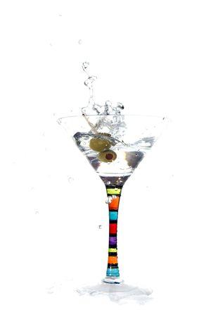 Olive falls into  martini glass creating splash