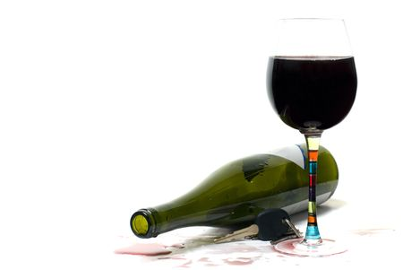 Bottle of red wine on side with full glass. Red wine has been spilled.  Car keys left on table