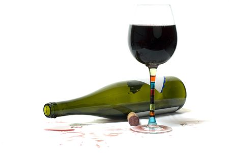 Bottle of red wine on side with full glass. Red wine has been spilled.
