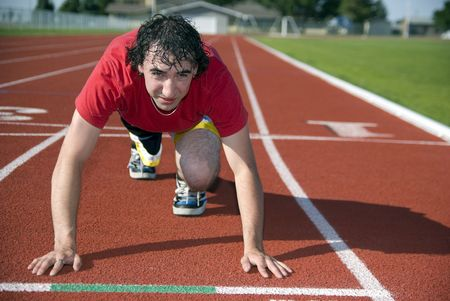 A young male adult is at the starting line of a track and field running event