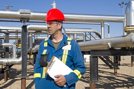 Male in full safety work gear inspects compressor site as daily duties Foto de archivo