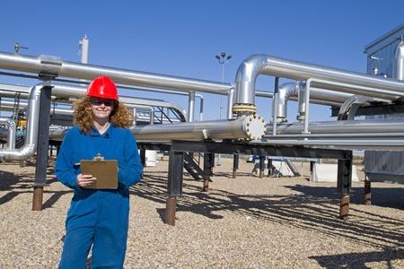 compresor: operador de campo de gas femenina en el equipo de seguridad completa completa tareas diarias