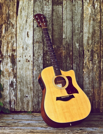 Vintage style image of a classical guitar on a grunge wood backdrop with copy space.  photo
