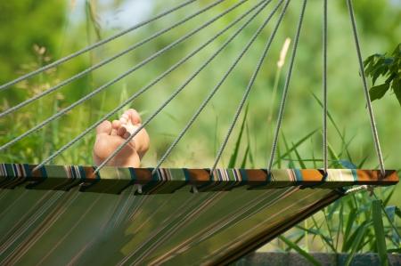 hamaca: Resumen de cerca la perspectiva de una hamaca con los pies hacia arriba en la sombra durante el verano.