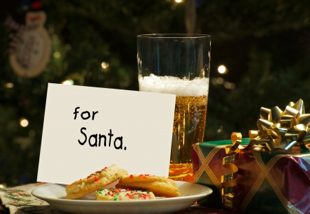 Abstract humorous image of a note left for Santa from the children on Christmas eve with cookies on a plate and a tall glass of cold beer with sparking Christmas lights and decorations