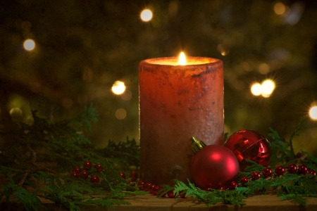A beautiful lit candle in front of a Christmas tree with sparkling lights and copy space  photo