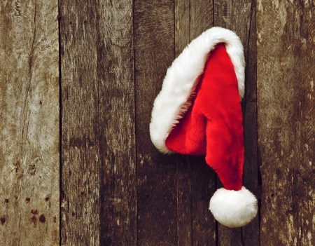 High contrast , antique textured vintage image of Santa s hat hanging on a rustic wooden backdrop with copy space