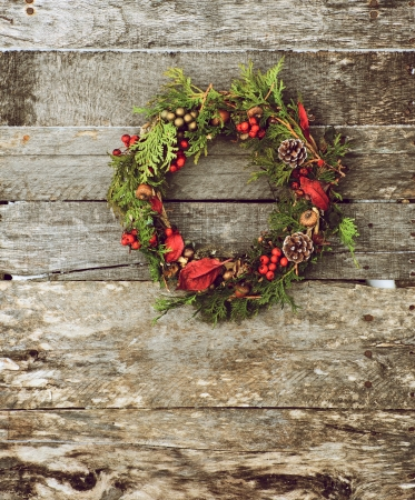 High contrast vintage style image of a home made christmas wreath with natural decorations hanging on a rustic wooden wall with copy space   Stock Photo