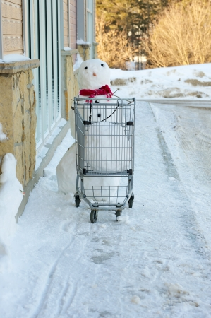 Humorous image of a snowman pushing a shopping cart with a big snowball in it with copy space Stock Photo - 15139331