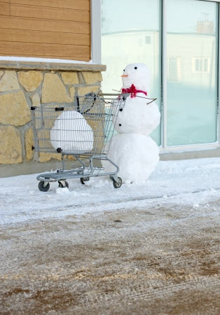 Humorous image of a snowman pushing a shopping cart with a big snowball in it with copy space