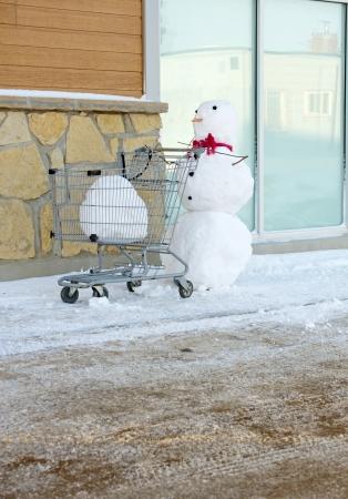 Image humoristique de bonhomme de neige poussant un caddie avec une grosse boule de neige en elle, avec copie espace