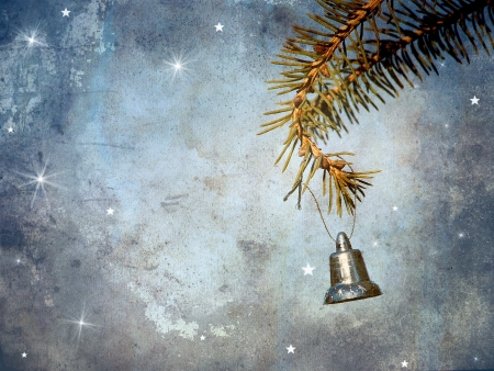 Vintage antique textured image for a Christmas card featuring a little silver bell hanging from a pine branch with whimsical designs and copy space    Stock Photo