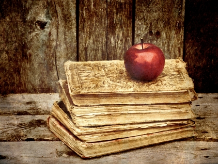 grunge textures: Heavily antique textured vintage image of a pile of antique books with an apple on a grunge background with copy space
