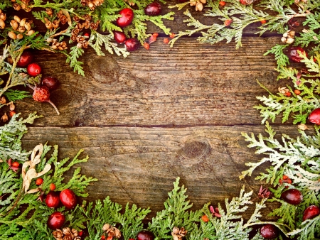 Richly toned Christmas background with cedar sprigs, berries, and maple keys on a grunge wood backdrop with copy space