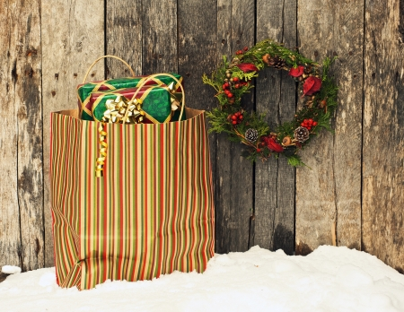 christmas gift: High contrast image of a home made christmas wreath with natural decorations hanging on a rustic wooden wall beside a colorful bag filled with christmas gifts