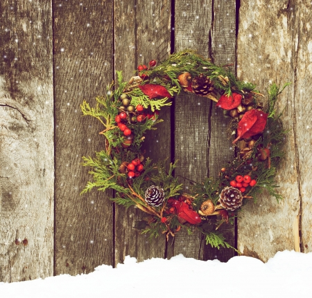 Richly toned vintage style image image of a home made christmas wreath with natural decorations hanging on a rustic wooden wall with snow and copy space
