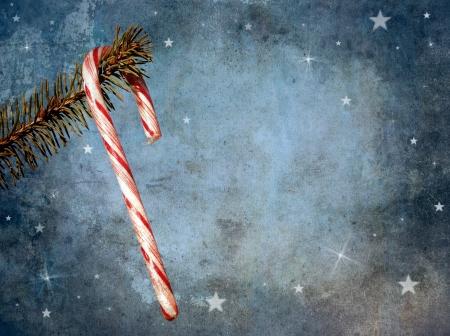 변덕스러운 디자인으로 소나무 지점에서 매달려 사탕 지팡이를 특징으로 크리스마스 카드 및 복사 공간 빈티지 스타일 골동품 질감 이미지