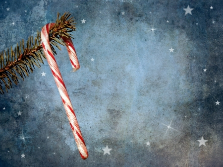candy cane: Vintage style antique textured image for a Christmas card featuring a candy cane hanging from a pine branch with whimsical designs and copy space