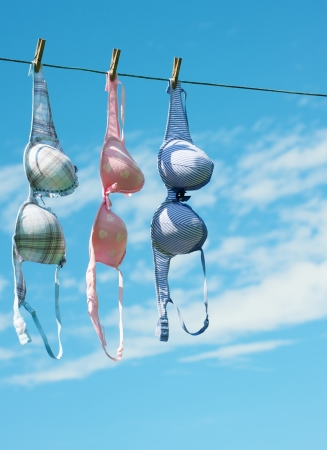 Three pretty women s bras hang in the fresh air and sunshine drying with copy space