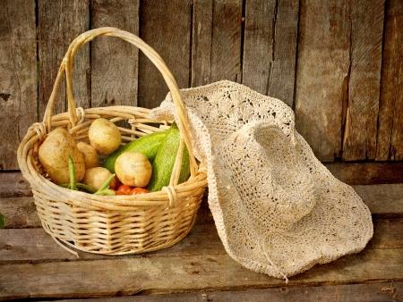 Vintage image textur�e d'un panier de l�gumes biologiques fra�ches cueillies et un chapeau de paille sur un fond de bois grunge Banque d'images